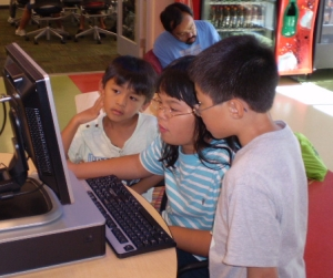 "This work, ""Kids at computer,"" is a derivative of ""Kids using the computers."" by San Jose Library, used under CC BY/Cropped from original"